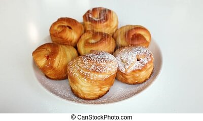 Sprinkling icing sugar on the fresh baked cruffins - Close-...