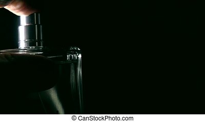 Sprinkling perfume against black background super slow...