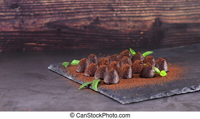 Sprinkling with cocoa chocolate truffles on slate - ...