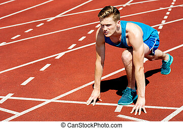 Sprinter getting ready to start the race - Young muscular...
