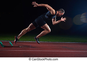 Sprinter leaving starting blocks on the running track....