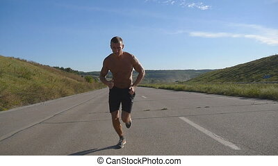 Sprinting runner man jogging at highway. Male sport athlete...