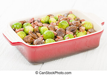 Sprouts, Chestnuts & Bacon - Brussels sprouts cooked with lardons and chestnuts on a white background. Traditional Christmas side dish.