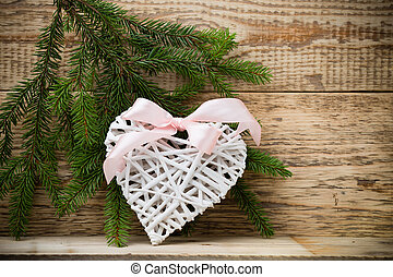 Spruce background. - Spruce branch with white braided heart...
