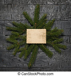Spruce branches with a sheet of old paper on a wooden table. Space for your text.