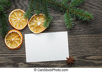 spruce twig with dried orange slices on oak table