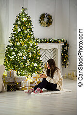 sprytny, ciemnowłosy, ruchomy, drzewo, telefon, dziewczyna, siada, boże narodzenie, hands.