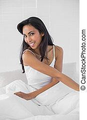 sprytny, kobieta uśmiechnięta, radośnie, na aparacie fotograficzny, posiedzenie, na, jej, łóżko