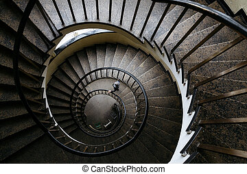 Spun circular staircase with a handrail in a building with people
