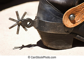 Back of a cowboy boot with a spur in bright sunlight.