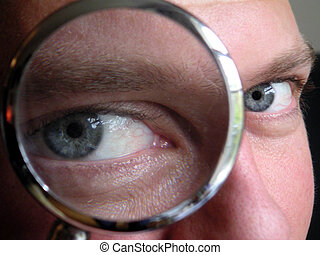 man looking through magnifying glass.