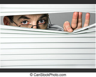 Spying - Close-up of venetian blind with male looking out of...