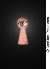 Spying - Creepy man peeking through a keyhole with focus on...