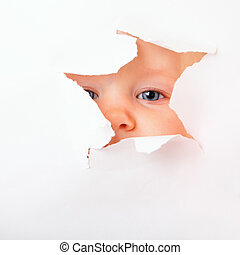 Spying - Cute baby girl looking through paper hole