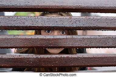 Spying - Teen girl looking through wet fence with water...