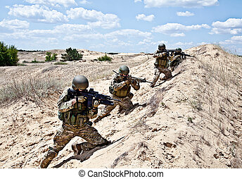Squad in action - Squad of soldiers in the desert during the...