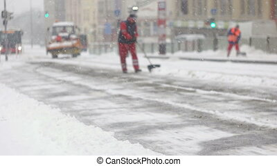 Squad of city workers cleaning snow from station - City...