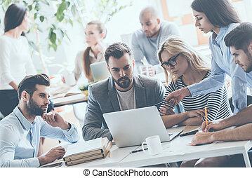 squadra, a, work., gruppo, di, giovane, persone affari, lavorativo, e, comunicare, mentre, seduta, ufficio, scrivania, insieme, con, colleghi, seduta, in, il, fondo