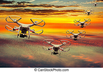 Squadron flying drones - Drones squadron in the sunset with...