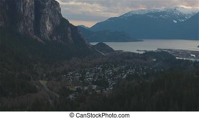 Squamish, North of Vancouver, British Columbia, Canada. View from the top of the Mount Crumpit of a small town surrounded by Canadian Mountain Landscape. Spring Sunset