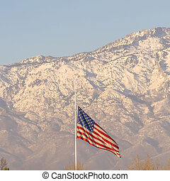Square American flag and building with Mount Timpanogos and sky in the background