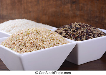 Square bowls of uncooked brown, white, and red and black rice on dark wood vintage background.