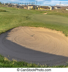 Square Close up view of a sand trap at a sunny golf course with houses in the distance