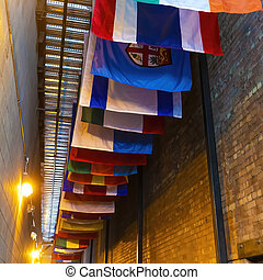 Square crop Vibrant colorful decorative flags against corrugated metal roof of building