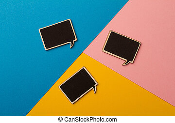 Top view of square chalk board speech bubbles on colored papers, metaphor, concept for communication