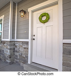 Square Facade of a home with a simple wreath hanging on the white wooden door