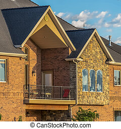 Square frame Beautiful home exterior with stone and brick wall against sky on a sunny day