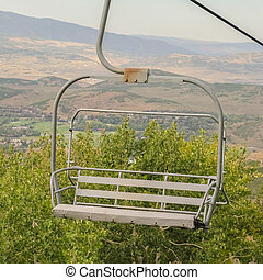 Square frame Close up of chairlift with aerial view of Park City ski resort during off season