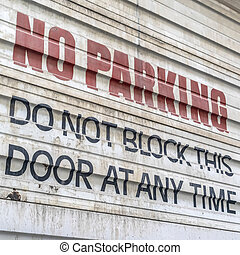 Square frame Close up of No Parking sign painted on the corrugated metal door of a building
