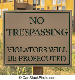 Square frame Close up of No Trespassing sign post beside a paved road that leads to houses
