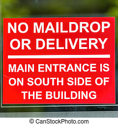 Square frame Close up of red No Maildrop Or Delivery sign on the glass wall of a building
