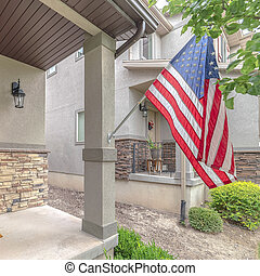 Square frame Front door of suburban home with American flag