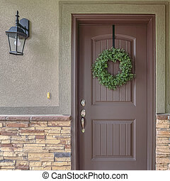 Square frame Front door of suburban home with green wreath