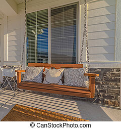 Square frame Front veranda of modern home with swinging chair