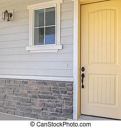 Square frame Front veranda of suburban home with a yellow door