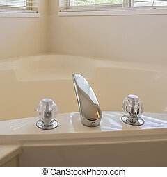 Square frame Gleaming heart shaped built in bathtub at the corner of a bathroom