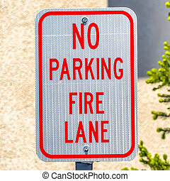 Square frame No Parking Fire Lane sign with a tree and wall in the background