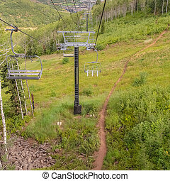 Square frame Off season in Park City with hiking trail amid grasses and chairlifts overhead