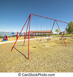 Square frame Swings on a park with playground pavilion lake and mountain in the background