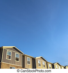 Square frame Townhouses with brick wood and concrete wall against blue sky on a sunny day