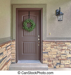 Square Front door of suburban home with green wreath