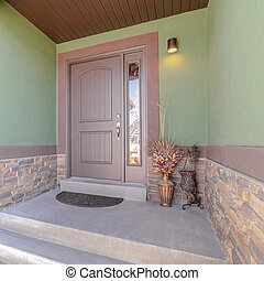 Square Front porch and door of traditional green home