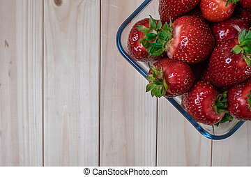 square glass bowl with strawberries on a light wooden table