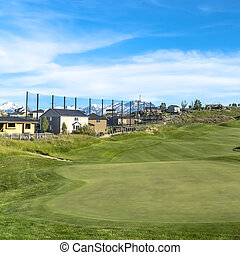 Square Golf course and homes under blue sky with clouds viewed on a sunny day