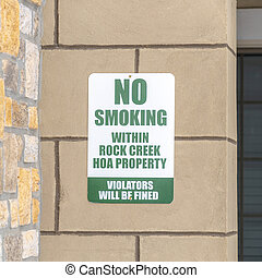 Square No Smoking sign on the exterior stone wall of apartment in Rock Creek Utah