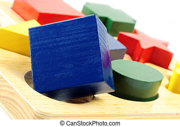 Square peg in a round hole. Wooden block shapes, with square block over round hole.